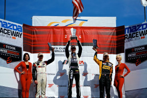 Michael Lewis holds high his trophy after earning the victory in the No. 98 Competition Motorsports/Curb-Agajanian Porsche 911 in the third race of the 2014 IMSA GT3 Cup Challenge USA by Yokohama season on Sunday, May 4. Photo by Blake Blakely.