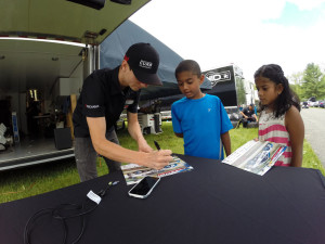 Michael Lewis makes some time from his busy race weekend schedule to meet and sign autographs for some young race fans.