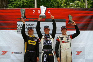 Michael Lewis shows off the trophy for taking the top spot on the podium for Round 12 of the IMSA Porsche GT3 Cup Challenge USA at Road America on Sunday, August 10.