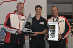 Michael Lewis earned Rookie of the Year honors this season after claiming four wins, six pole positions and nine podium appearances. Here, he accepts the award from Porsche Motorsport North America's Ralph Hollack (left) and Eric Bloss (right).