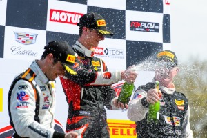 Celebrating his first GT win, Michael Lewis sprays the champagne on top of the PWC podium on Saturday, March 12, 2016.