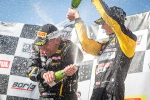 Preston Calvert (left) and Michael Lewis celebrate on the podium as they co-drove to two wins in the PWC SprintX category at Utah Motorsports Campus on August 13 and 14, 2016.